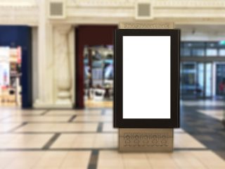Emptyportrait digital signage with blurred mall background. Ideal for digital advertisement, information board, mall ads, video wall and large posters for campaigns